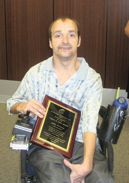 Picture of John Britton holding an award